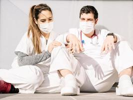 trötta läkare som sover på golvet på klinikens terrass tillsammans foto