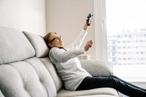 upphetsad äldre kvinna med controller som spelar videospel foto