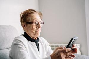 äldre kvinna som använder smartphone hemma foto