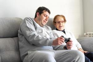 vuxen man och äldre kvinna med gamepad hemma foto