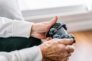 beskära äldre kvinna med gamepad hemma foto