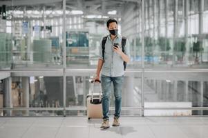 asiatisk man med ansiktsmask med bagage med smartphone foto