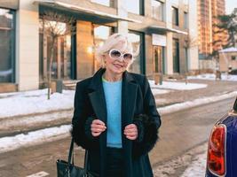 äldre elegant kvinna i elegant svart kappa och handväska som går från hennes bil till affärsmöte. företag, stil, anti age koncept foto