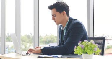 affärsmän som använder anteckningsbok och fyller allvar med arbetet tills huvudvärk foto