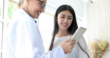 läkarmöte och förklarar medicinering för kvinnlig patient på hans kontor på sjukhus foto
