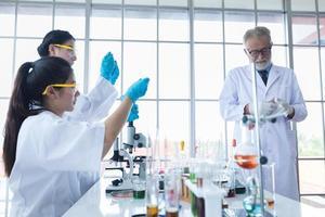 medicinsk forskning och forskare arbetar med ett mikroskop och en tablett och provrör, mikropipett och analysresultat i ett laboratorium. foto