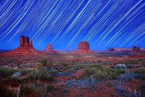 dagsljus och stjärnspårbild av monument valley arizona usa foto