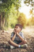 glad pojke som sitter och tänker ensam i parken foto