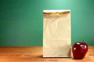 skol lunch lunch säck sitter på lärare skrivbord foto