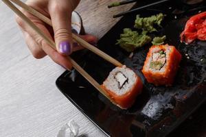 sushi. hand med ätpinnar foto