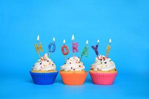 födelsedagsmuffins med ljus som säger hurra foto