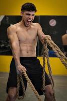 muskulös kraftfull aggressiv man som tränar med rep i funktionell träning fitness gym foto