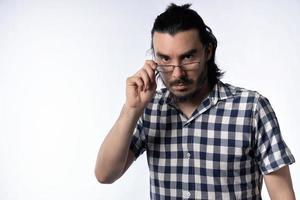 närbild av ensam man, med skägg och glasögon, tittar på kameran som håller glasögon för att titta över dem. foto
