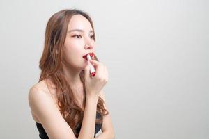 porträtt vacker kvinna sminkar och använder rött läppstift foto