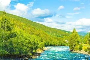 turkos smältvatten rinner i floden genom bergslandskapet i Norge foto