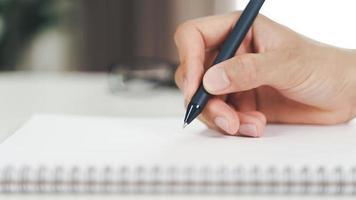 närbild av ung man i vardagliga tyghänder som skriver ner på anteckningsblocket, anteckningsbok med kulspetspenna på bordet. foto