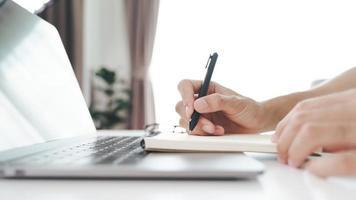 närbild av ung man i casual tyg händer som skriver ner på anteckningsblock, anteckningsbok med kulspetspenna med bärbar dator på bordet. foto