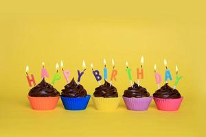 färgglada grattis på födelsedagen muffins med ljus foto