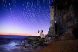 ensam tjej som tittar mot havet med en lykta som söker foto