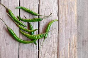 grön rå chili på träbakgrund foto