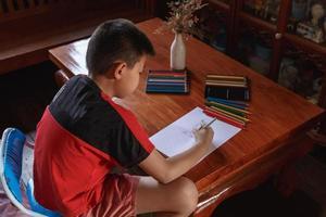en pojke sitter hemma och tecknar och målar. foto