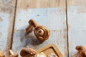 färska shiitakesvampar på köksbordet i trä foto