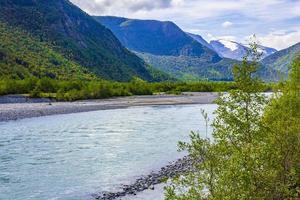 turkos smältvatten rinner i en flod genom norska berg foto