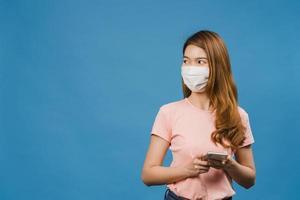 ung asiatisk tjej som bär medicinsk ansiktsmask med mobiltelefon med klädda i vardagskläder isolerad på blå bakgrund. självisolering, social distansering, karantän för förebyggande av corona-virus. foto