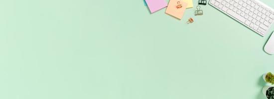 kreativt plattläggningsfoto av skrivbordet på arbetsytan. ovanifrån kontorsbord med tangentbord, mus och bok på pastellgrön färgbakgrund. panoramabanner med kopieringsutrymme för text och reklamområde. foto