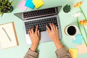 kreativt plattläggningsfoto av skrivbordet på arbetsytan. ovanifrån kontorsbord med bärbar dator, kaffekopp och öppen mockup svart anteckningsbok på pastellgrön färgbakgrund. ovanifrån håna med kopia utrymme fotografering. foto