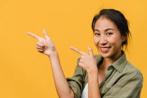 porträtt av ung asiatisk dam som ler med glatt uttryck, visar något fantastiskt på tomt utrymme i vardagsduk och tittar på kameran isolerad över gul bakgrund. ansiktsuttryck koncept. foto