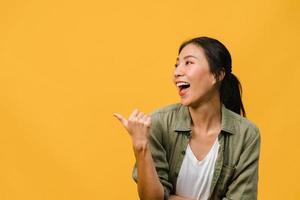 porträtt av ung asiatisk dam som ler med glatt uttryck, visar något fantastiskt på tomt utrymme i vardagskläder och står isolerat över gul bakgrund. ansiktsuttryck koncept. foto