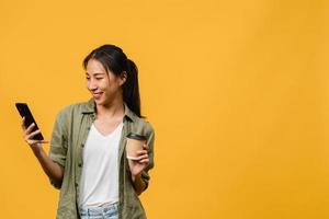 ung asiatisk dam som använder telefonen och håller kaffekoppen med positivt uttryck, ler brett, klädd i avslappnad trasa som känner lycka och står isolerad på gul bakgrund. ansiktsuttryck koncept. foto