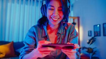 glad asien tjej spelare bär hörlurstävling spela videospel online med smartphone färgglada neonljus i vardagsrummet hemma. esport -strömmande spel online, hemmakarantänaktivitetskoncept. foto