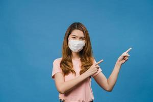 ung asiatisk tjej som bär medicinsk ansiktsmask visar något på tomt utrymme med klädd i vardagsduk och tittar på kameran isolerad på blå bakgrund. social distansering, karantän för corona. foto