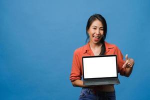 ung asiatisk dam visar tom bärbar datorskärm med positivt uttryck, ler brett, klädd i vardagskläder som känner lycka isolerad på blå bakgrund. dator med vit skärm i kvinnlig hand. foto