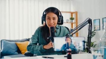 tonåring asien flicka influencer använda mikrofon bära hörlurar spela in innehåll med smart telefon för online publik lyssna hemma. student kvinnlig podcaster gör ljudpodcast från hennes hemstudio. foto