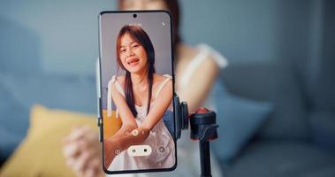 glad ung asiatisk tjejbloggare framför telefon kamera använda surfplatta njuta av frågesvar med följare i vardagsrummet hemma. bloggare aktivitets livsstil, socialt avstånd coronavirus pandemi koncept. foto