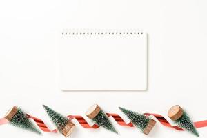 minimal kreativ lägenhet av vinterjulens traditionella komposition och nyårshelger. ovanifrån öppen mockup svart anteckningsbok för text på vit bakgrund. håna och kopiera rymdfotografering. foto