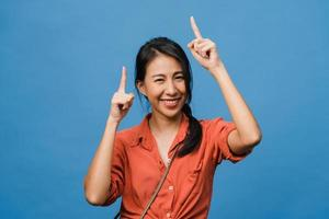 porträtt av ung asiatisk dam som ler med glatt uttryck, visar något fantastiskt på tomt utrymme i vardagsduk och tittar på kameran isolerad över blå bakgrund. ansiktsuttryck koncept. foto