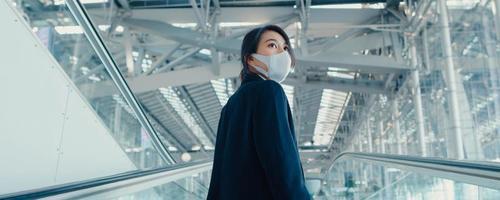 asiatisk affärsflicka bära ansiktsmask dra bagage stå på rulltrappa titta runt promenad till terminal på internationella flygplats. affärsresor social distansering koncept. panoramabanner bakgrund. foto