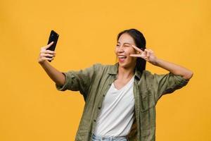 le bedårande asiatisk kvinna som gör selfie foto på smart telefon med positivt uttryck i vardagskläder och stativ isolerad på gul bakgrund. glad förtjusande glad kvinna jublar över framgång.