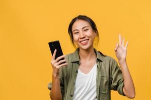 förvånad ung asiatisk dam med mobiltelefon med positivt uttryck, le brett, klädd i vardagskläder och titta på kameran på gul bakgrund. glad förtjusande glad kvinna jublar över framgång. foto