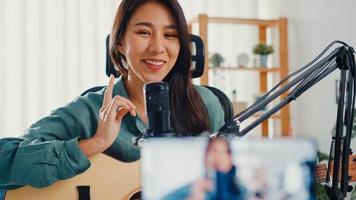 tonåring asien flicka influencer spela gitarr musik använda mikrofon inspelning med smartphone för online publik lyssna hemma. kvinnlig podcaster gör ljudpodcast från hennes hemmastudio, stanna hemma -konceptet. foto