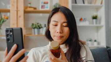 sjuk ung asiatisk kvinna hålla medicin sitta i soffan videosamtal med telefon konsultera läkare hemma. tjej tar medicin efter läkarorder, karantän hemma, socialt distanserat coronavirus -koncept. foto