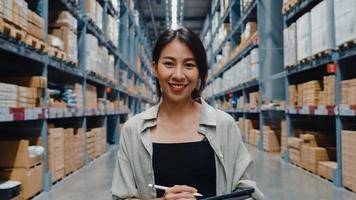 porträtt av attraktiva unga asiatiska affärskvinna chef leende charmigt titta på kameran hålla digital tablett stativ i detaljhandeln köpcentrum. distribution, logistik, paket redo för leverans. foto