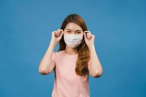 ung asiatisk tjej bär medicinsk ansiktsmask med klädda i vardagskläder och tittar på kameran isolerad på blå bakgrund. självisolering, social distansering, karantän för förebyggande av corona-virus. foto