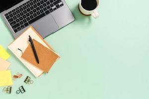 minimalt arbetsutrymme - kreativt plattläggningsfoto av arbetsytans skrivbord. ovanifrån kontorsbord med bärbar dator, kaffekopp och anteckningsbok på pastellgrön bakgrund. ovanifrån med fotografering av kopieringsutrymme. foto