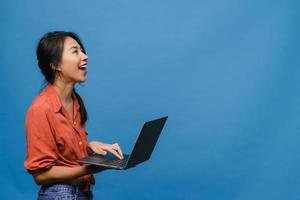 ung asiatisk dam som använder bärbar dator med positivt uttryck, ler brett, klädd i vardagskläder som känner lycka och står isolerad på blå bakgrund. glad förtjusande glad kvinna jublar över framgång. foto
