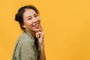 ung asiatisk dam med positivt uttryck, le brett, klädd i vardagskläder och titta på kameran över gul bakgrund. glad förtjusande glad kvinna jublar över framgång. ansiktsuttryck koncept. foto